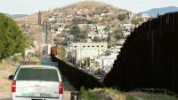 米アリゾナ州ノガレスから見た対メキシコ国境に設置された高さ6メートルの鉄柵の壁。よじ登って米国に侵入する移民の姿を「ほぼ毎日」目撃している住民たちは、トランプ大統領の壁建設令にも冷ややかな視線を向けて暮らしている=20170203- 写真提供:時事通信