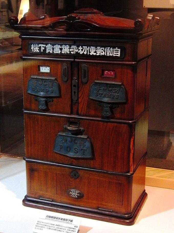 現存する日本最古の自動販売機「自働郵便切手葉書売下機」(展示はレプリカ)。明治37年(1904年)に発明家の俵谷高七が作成した。逓信総合博物館の展示。(wikipediaより)