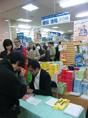 サインを書く飯田さん.JPG